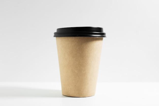 Gros plan d'une tasse en papier jetable pour le café à emporter, avec couvercle noir, isolé sur blanc.