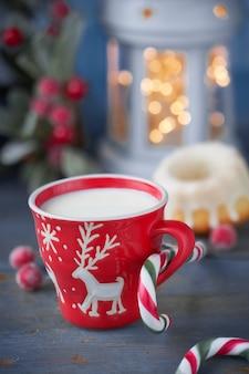 Gros plan sur une tasse rouge avec du lait et des décorations de noël