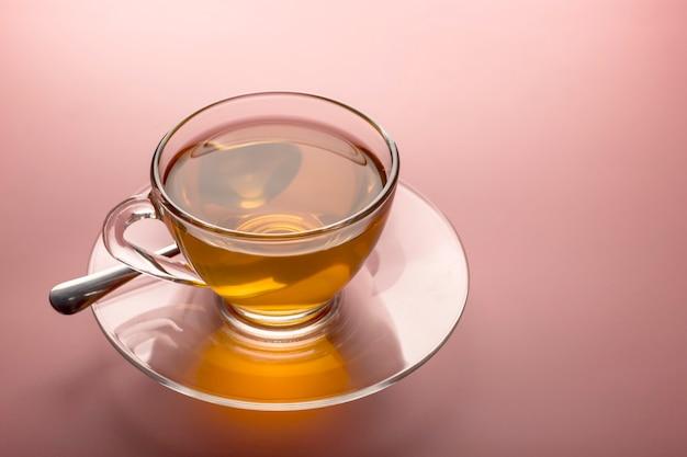 Gros plan de la tasse de thé chaude en verre transparent sur fond rose.