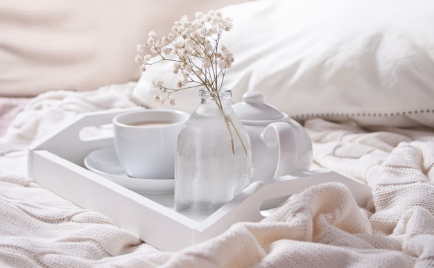 Gros plan d'une tasse de thé, lait, théière et bouquet de fleurs blanches sur le plateau blanc.