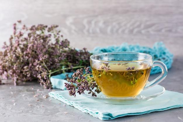 Gros plan sur une tasse de thé à l'origan et un bouquet d'herbes sèches à proximité