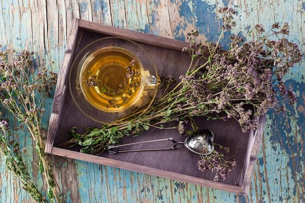 Gros plan sur une tasse de thé à l'origan et un bouquet d'herbes sèches