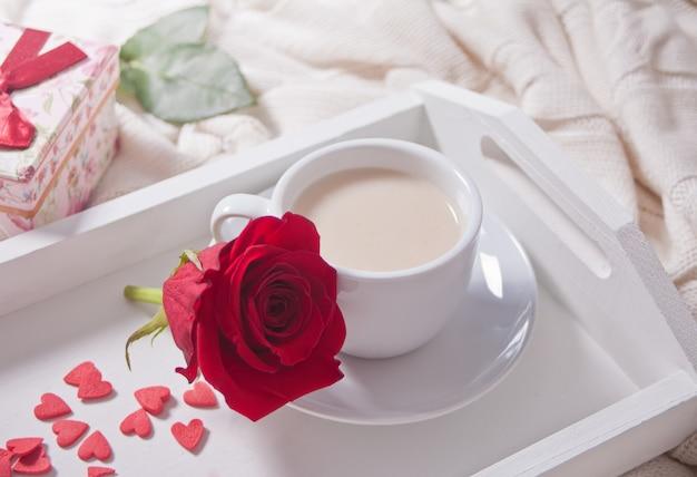 Gros plan d'une tasse de thé avec une rose rouge sur le plateau blanc