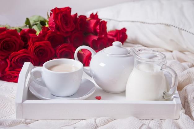 Gros plan d'une tasse de thé avec des roses rouges sur le plateau blanc