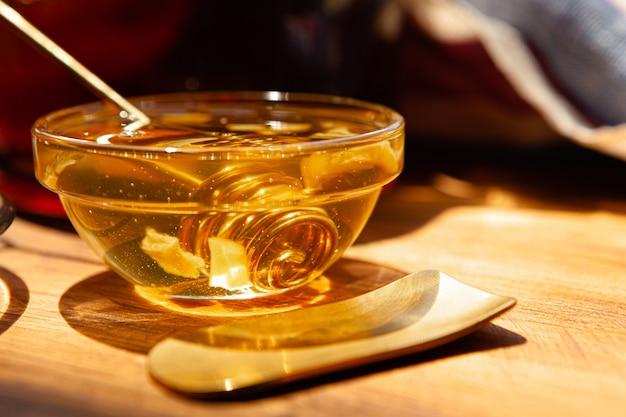 Gros plan d'une tasse de thé en verre avec du miel