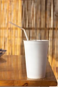 Gros plan sur une tasse et un tube jetables blancs vierges à emporter sur une table en bois et avec un mur de bambou comme arrière-plan flou. heure d'été.
