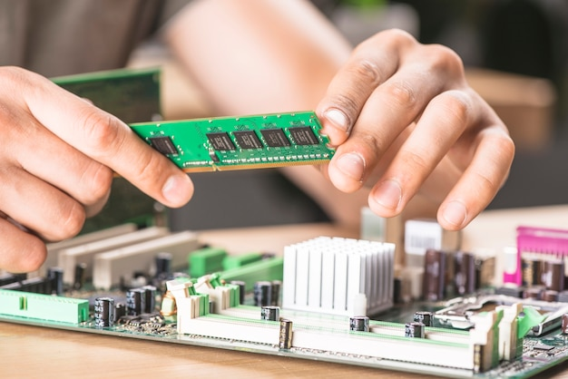 Gros plan d'un technicien informatique mâle qui installe de la mémoire vive dans la carte mère