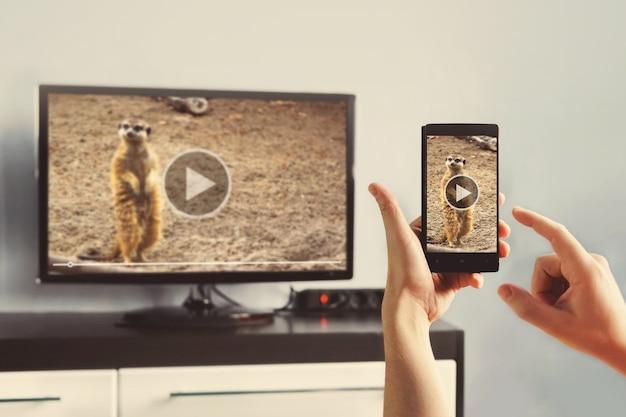 Le gros plan d'un téléphone intelligent est connecté à un téléviseur intelligent.
