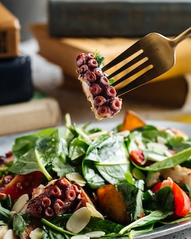 Gros plan sur tentacule de poulpe sur une fourchette de manger une salade aux épinards