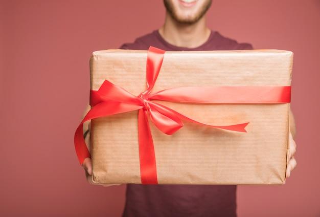 Gros plan, de, tenue homme, papier brun, emballé, boîte cadeau, à, ruban rouge, arc
