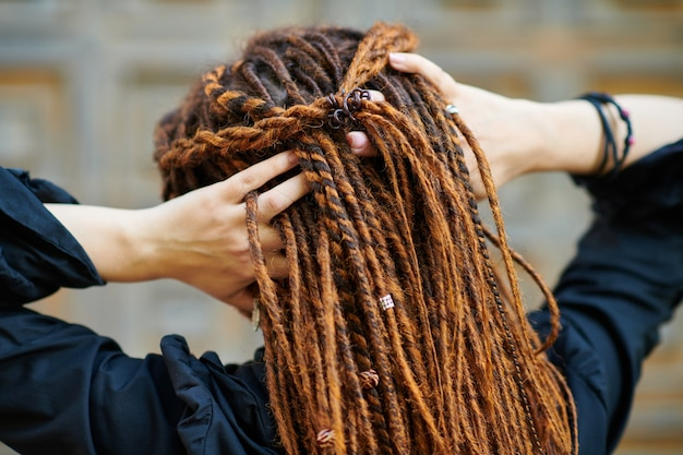 Gros plan de la tête de dreadlocks arrière, fille à la mode posant au vieux fond de porte en bois