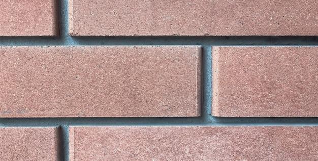 Gros plan sur la texture de la brique de revêtement. décoration extérieure des murs et des fondations des bâtiments, concept de construction.