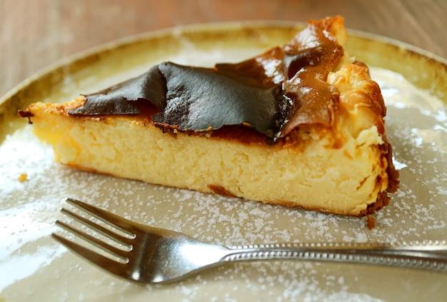 Gros plan sur la texture d'un délicieux gâteau au fromage basque fait maison servi sur une assiette de style rustique