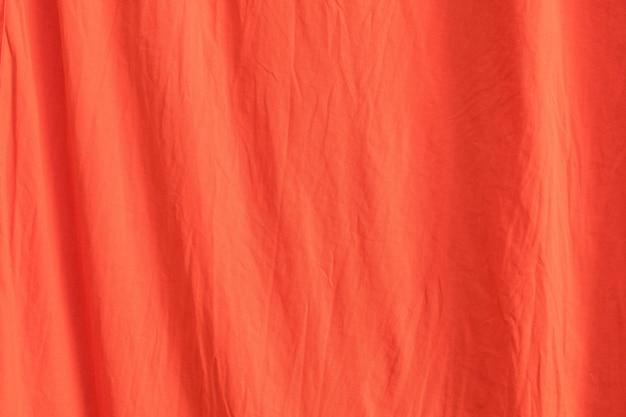 Gros plan de la texture du fond de tissu rouge orange.