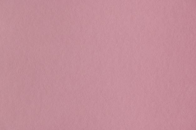 Gros plan de la texture du papier rose sans couture pour le fond ou les œuvres d'art