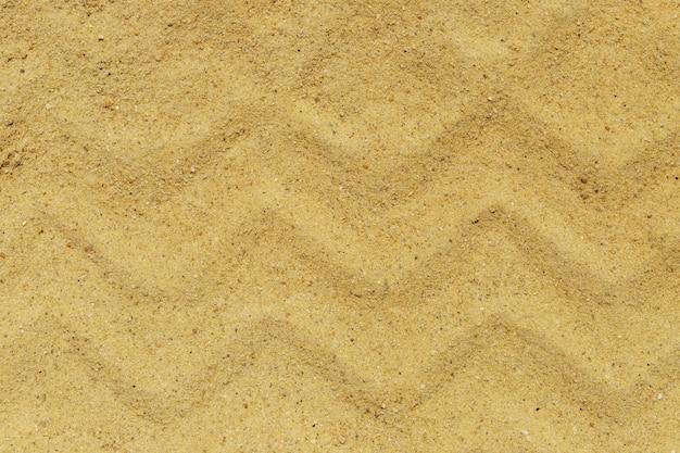Gros plan de la texture du sable avec des marques de pneus