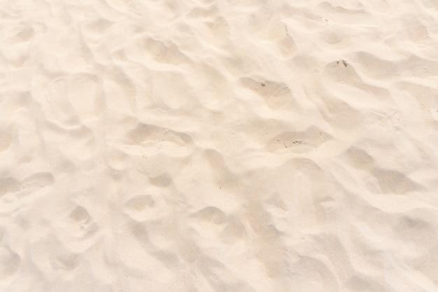 Gros plan sur la texture du sable de la plage jaune en arrière-plan