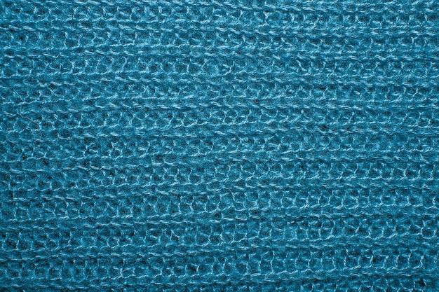 Gros plan sur la texture de la fourrure en laine tricotée. pull bleu en fil tissé moelleux en arrière-plan.