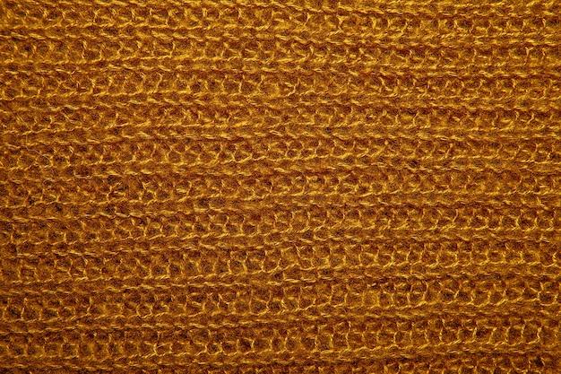 Gros plan sur la texture de la fourrure en laine tricotée. pull en fil tissé moelleux moutarde en arrière-plan.
