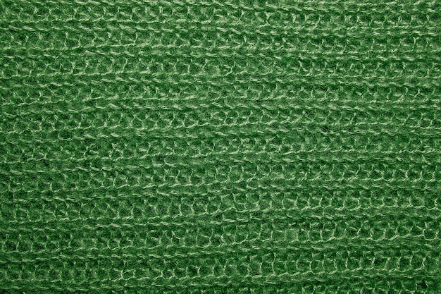 Gros plan sur la texture de la fourrure en laine tricotée. pull vert en fil tissé moelleux en arrière-plan.