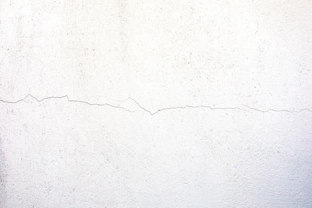 Gros plan d'une texture de mur de béton fissuré et patiné