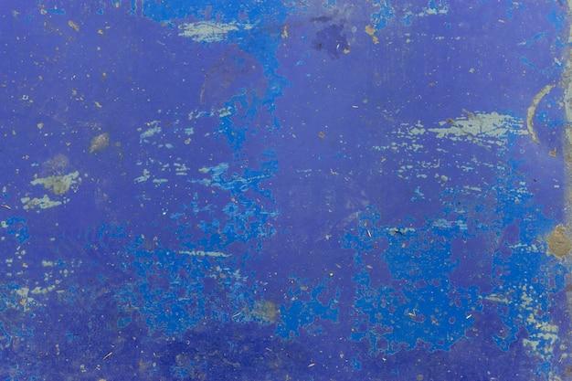 Gros plan d'une texture de mur bleu pelé. fond de vue de dessus