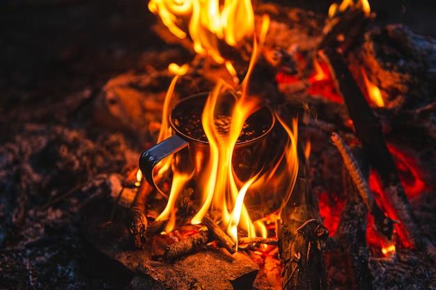 Gros plan de thé dans une tasse en métal se réchauffe dans un feu de joie