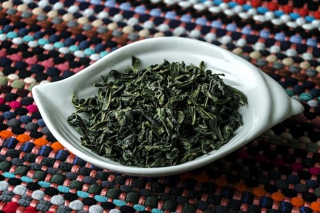 Gros plan de thé vert dans une assiette blanche sur une nappe colorée