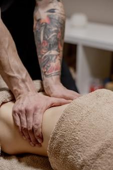 Gros plan d'un thérapeute faisant un massage de l'estomac sur une femme au spa.