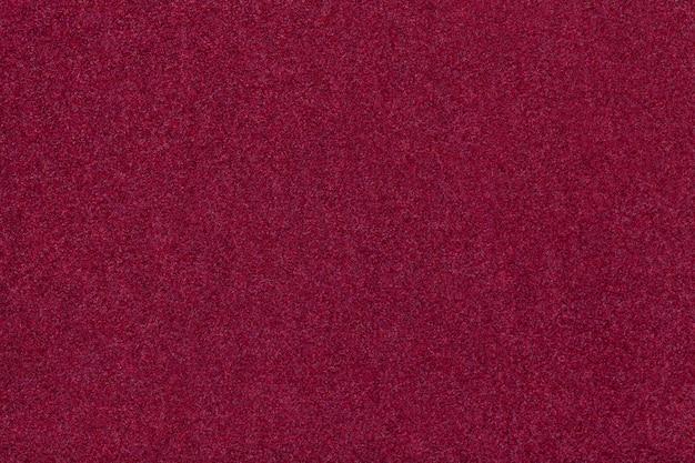 Gros plan de tissu en daim mat rouge foncé. texture velours de feutre.