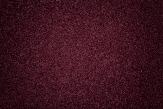 Gros plan de tissu en daim violet foncé mat. texture velours de feutre.