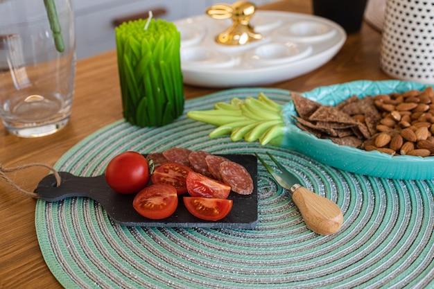 Gros plan sur des tomates cerises fraîches avec des tranches de saucisse à bord, un plateau d'amandes et des craquelins sur un comptoir en bois avec une bougie en forme et un plateau d'oeufs avec un lapin de pâques sur le dessus.