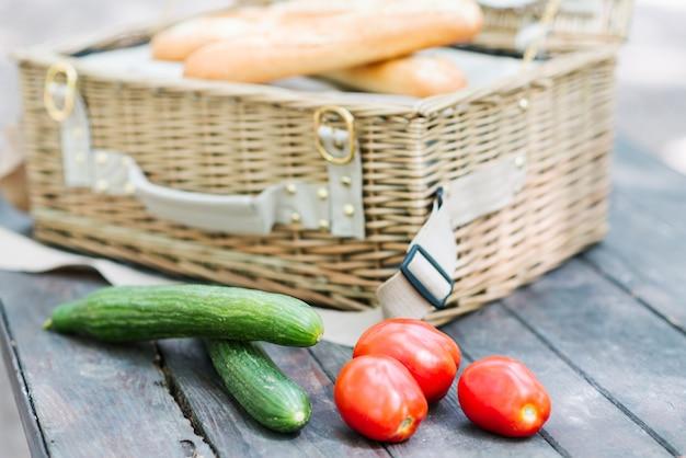 Gros plan des tomates et des concombres sur une table en bois devant un panier pique-nique ouvert.