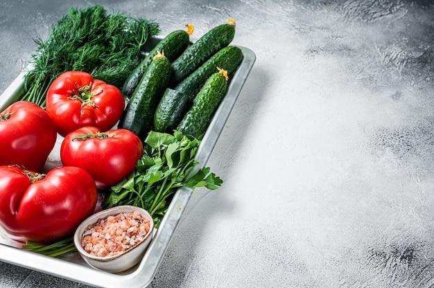 Gros plan de tomates rouges et de concombres verts aux herbes dans un plateau de cuisine. fond blanc. vue de dessus. espace de copie.
