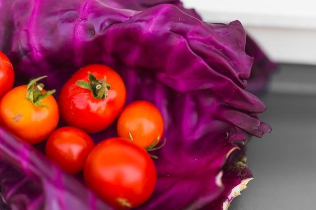 Gros plan, de, tomates rouges, sur, feuilles de chou pourpre