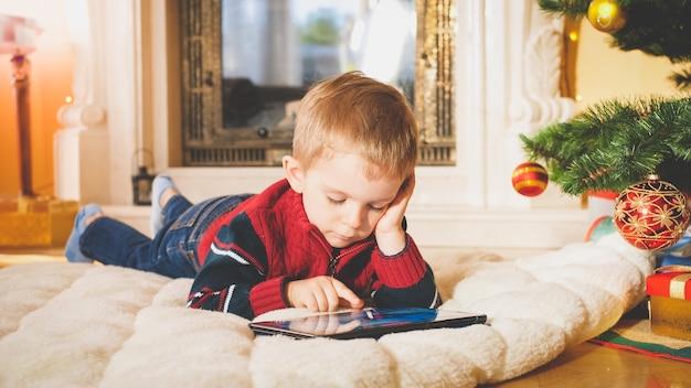 Gros plan tonique portrait de petit garçon allongé sous l'arbre de noël sur un tapis moelleux et jouant sur une tablette numérique