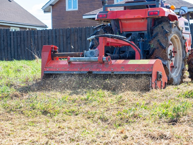 Gros plan d'un tracteur avec une tondeuse à chaîne coupant l'herbe sèche. entretien du territoire, paillage de l'herbe, machinerie agricole.