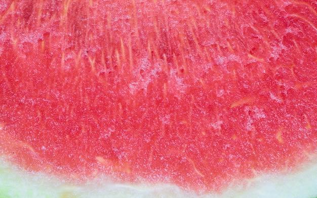 Gros plan d'une tranche fraîche de fond texturé de melon d'eau rouge.