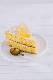 Gros plan d'une tranche de gâteau au citron décorée dans une assiette blanche avec une cuillère