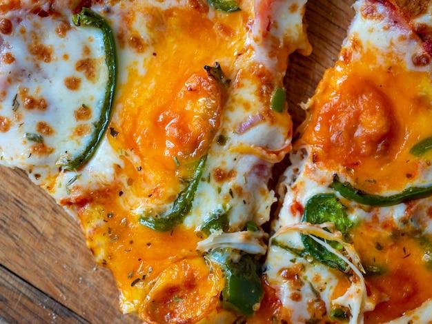 Gros plan d'une tranche de pizza au poivre vert. vue de dessus, mise à plat. plat italien, collation rapide