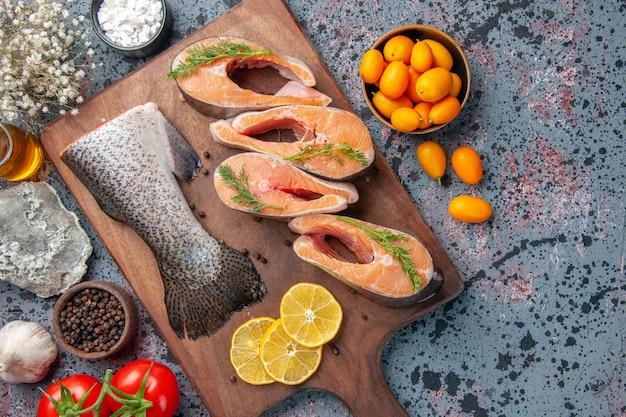 Gros plan de tranches de citron poissons crus poivre vert sur planche à découper en bois et fleur sur tableau de couleurs noir bleu