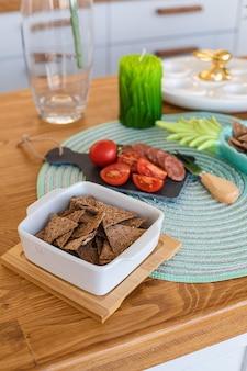 Gros plan sur des tranches de craquelins sains dans une assiette blanche avec des tomates fraîches coupées sur un tableau noir avec des saucisses.