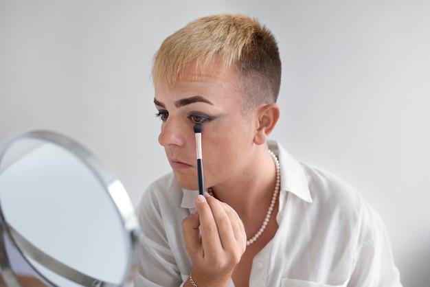 Gros plan sur un transgenre à l'aide d'un pinceau de maquillage