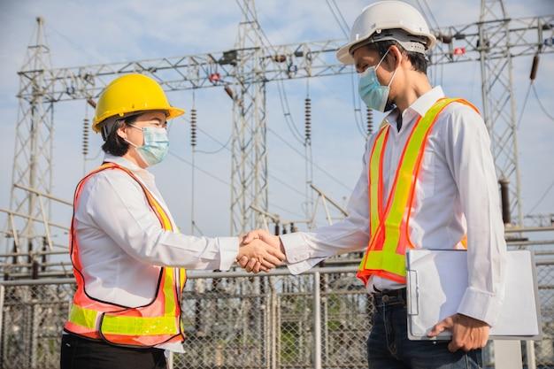 Gros plan sur le travail d'équipe de poignée de main, l'ingénieur serre la main de travail d'équipe et porte un masque préventif covid19