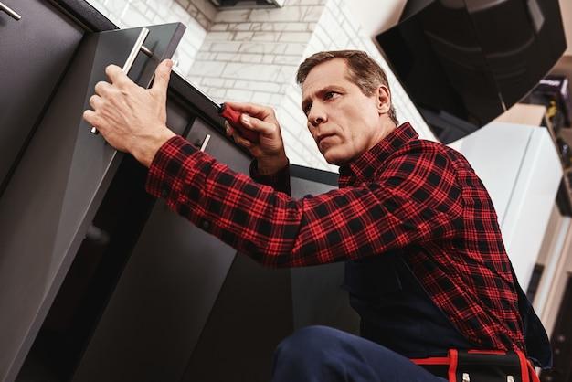 Gros plan de travail méticuleux de bricoleur senior réparant des armoires de cuisine