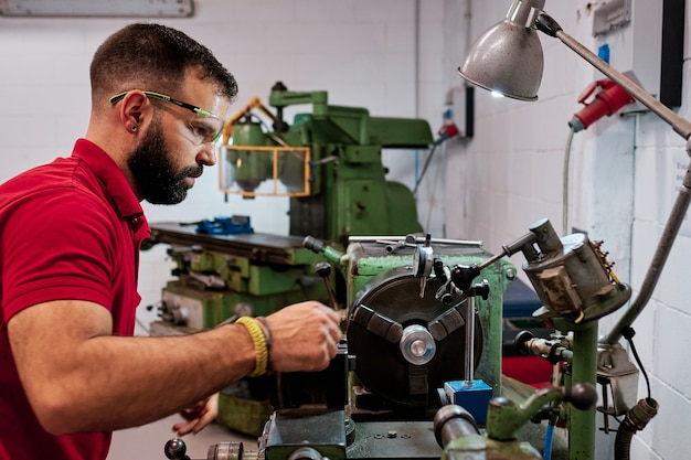 Gros plan travailleur dans des lunettes uniformes et protectrices travaillant sur l'affûtage de la machine-outil