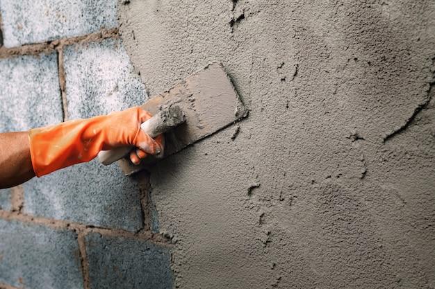 Gros plan travailleur à la main plâtrer le ciment sur le mur pour la construction d'une maison