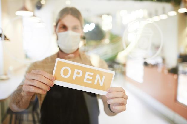 Gros plan d'un travailleur masculin de café portant un masque et tenant une pancarte ouverte sur une porte en verre, espace pour copie