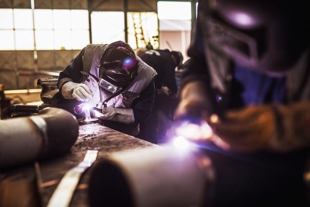 Gros plan d'un travailleur de tissu masculin coupe des tuyaux métalliques avec une meuleuse électrique en atelier.