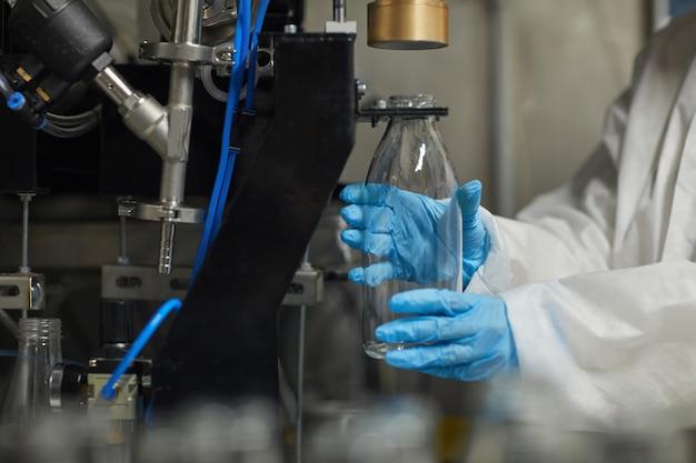 Gros plan d'une travailleuse méconnaissable désinfectant des bouteilles tout en travaillant dans une usine alimentaire, espace de copie